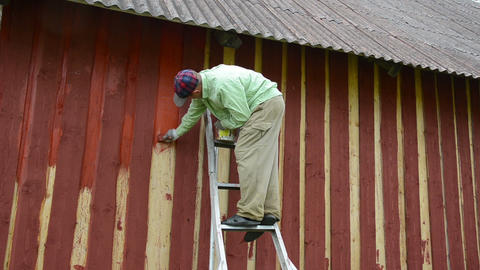 painter on ladder to the house wall paint wall with thick brush Live Action