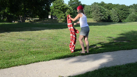 Woman girl with headscarf on head shake rug and flex it in park Footage