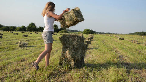 Attractive young woman dressed in short carry stack bales of hay Footage