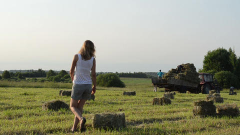 Pretty farmer woman girl carry bales of hay straw toward tractor Footage