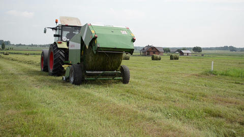 tractor baler discharge round fresh hay bale during harvesting Footage