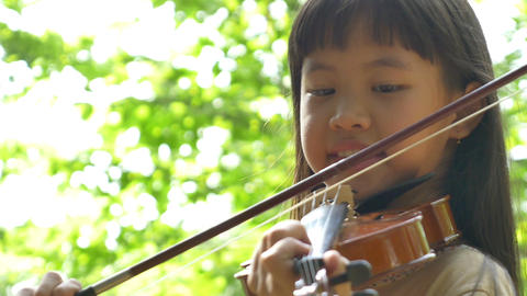 Little Asian girl playing violin in the park Footage