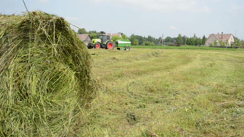 Closeup of hay bale and blurred machine tractor collect straw Footage