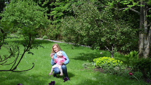 mother daughter blowing soap bubbles garden the trees flowers Footage