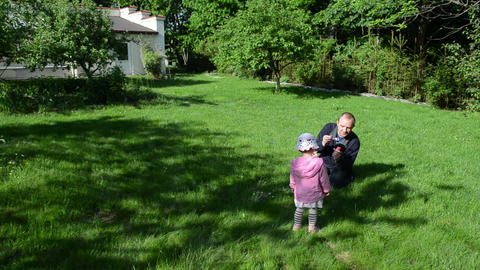 father blowing soap bubbles in garden. Girl clapping hands Footage