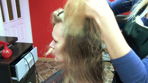 hairdresser comb separate strands customer long blonde hair Footage