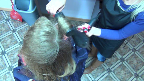 Closeup of stylist hands dry client woman hair with hairdryer Footage