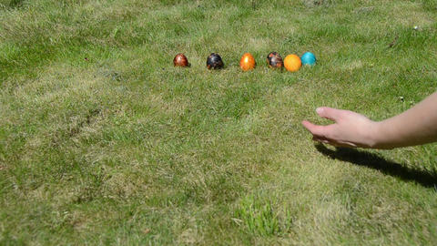 Hand put colorful painted eggs in a row and throw them to crash Footage