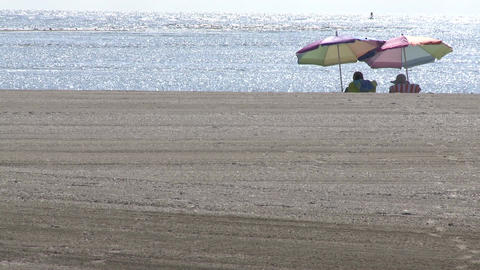 Two people under beach umbrellas on sand Footage