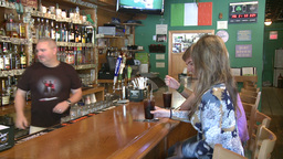 Woman and young man being served sodas at bar Footage