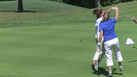 Female golfer sinks putt Footage