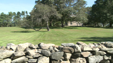 Stone wall around a home with grassy field and trees (1 of 2) Footage