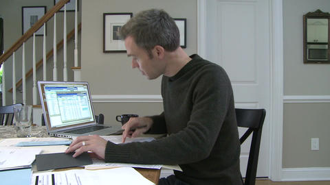 A man going to dining room table to work on his finances (3 of 4) Footage