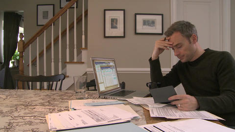 A man going over his bills on his dining room table (2 of 3) Live Action