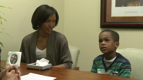 Young boy and mom talk with doctor Footage