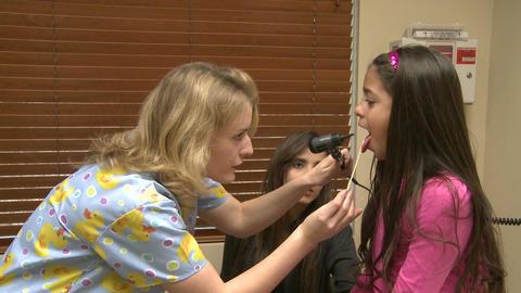 Nurse examines a patients sore throat Footage