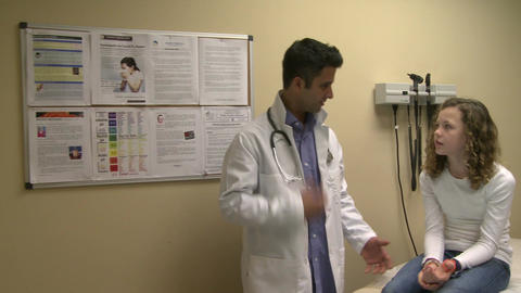 Doctor has friendly discussion with young patient Footage
