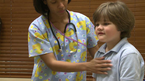 Female nurse gives young boy a checkup Footage