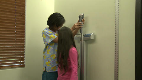 Nurse measures young female patient's height Footage