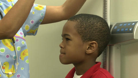 Young boy waits to have his height measured Footage