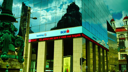 BUCHAREST, ROMANIA - June 2015,CEC Palace Mirrored In A Modern Building,Zoom Out stock footage