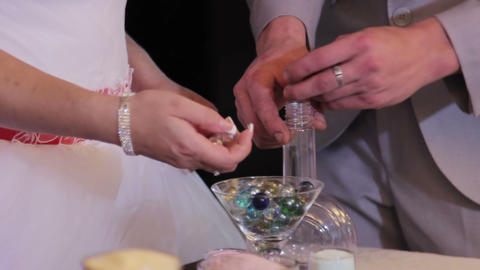 sand ceremony being performed at wedding. Hands of bride holding vase with color Footage