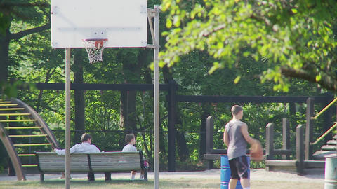 Teenage boy shooting hoops in park Footage