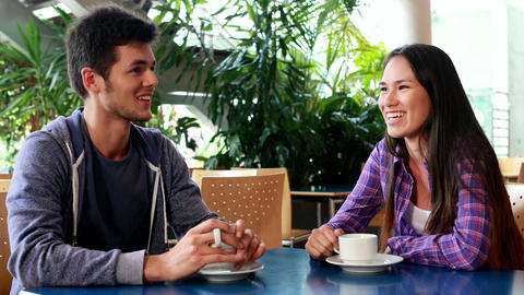 Smiling friends drinking coffee and speaking together Footage