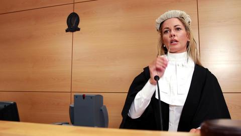 Judge speaking while banging gavel on sounding block Footage