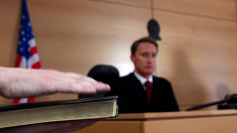 Judge looking at the witness swearing on bible Footage