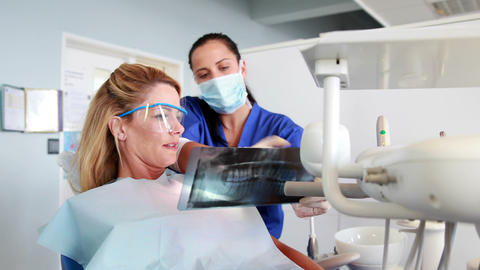 Dentist explaining x-ray report to her patient Footage