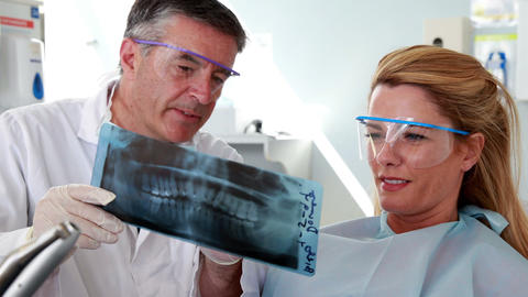 Dentist and patient in protective glasses looking x-ray together Footage