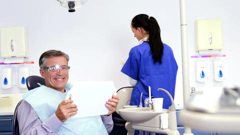 Patient admiring his new smile in the mirror Footage