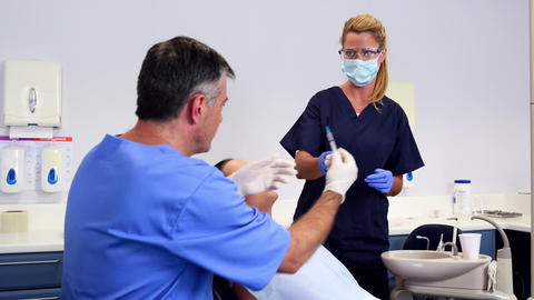 Dentist about to giving patient an injection Footage
