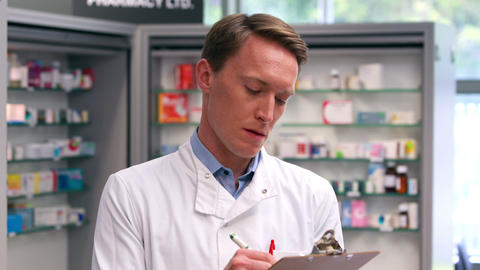 Handsome pharmacist writing on clipboard Footage