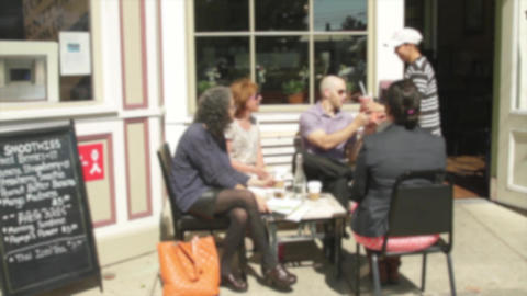 People sitting outside a small cafe on sidewalk (2 of 3) Live Action