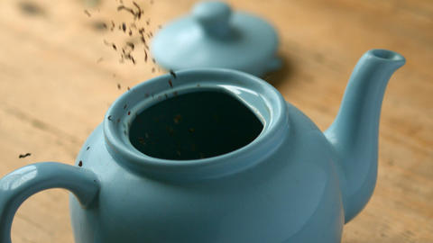 Loose tea pouring into blue teapot Footage