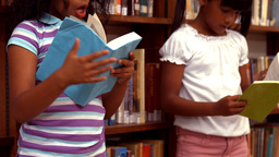 Cute pupils reading in the library Footage