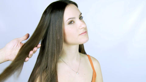 Hairdresser ironing long hair of a female model Stock Video Footage