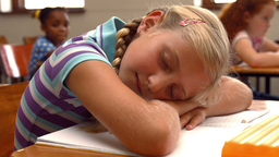 Schoolchild napping on notepad at school Live Action