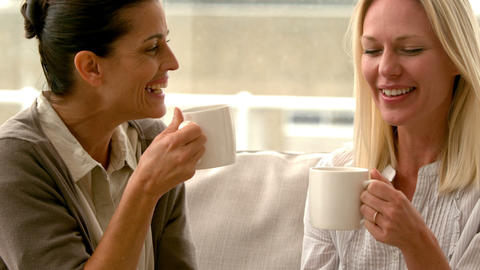 In slow motion two friends sitting on the couch chatting over coffee at home Footage