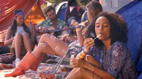 In high quality format carefree hipster blowing bubbles in tent Footage
