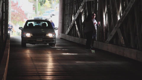 Cars and pedestrians entering covered bridge (4 of 4) Footage
