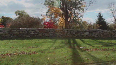 Driving by stone wall bordering residence Footage