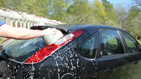 Closeup of man wash black favorite car with foam and sponge Footage