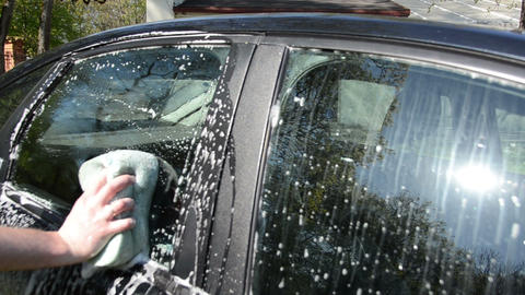 Closeup of hand with soapy sponge clean wash car glass Footage