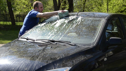 Young man carefully wash his favorite car windscreen and roof Live Action