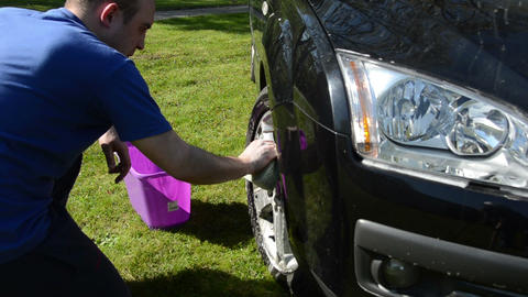 man wash his favorite car wheels with soap and sponge on lawn Footage