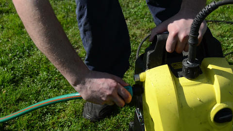 man hand detach water hose to high pressure wash equipment Footage