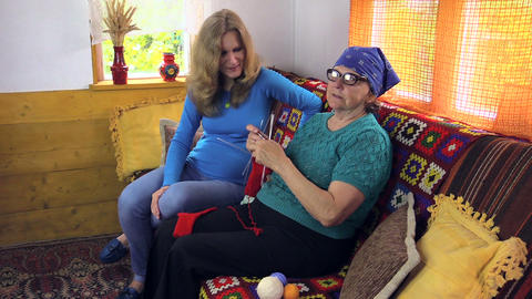 grandma knit sock talk with pregnant granddaughter in room Footage
